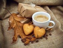 Een koffie met een koekje in de vorm van harten op een retro achtergrond Stock Afbeeldingen