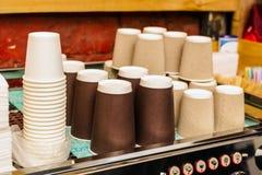Een koffiemachine met een grote stapel document koppen naast het Stock Fotografie