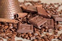 Een koffiepot, geroosterde koffiebonen, pijpjes kaneel en stukken van chocolade op een jute Stock Foto's
