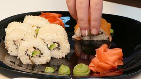Een kok maakt een reeks sushibroodjes op een plaat stock video