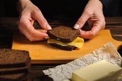 Een kok maakt een sandwich van brood en kaas royalty-vrije stock foto's