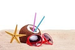 Een kokosnoot, zeester en zonnebril op een strand Stock Afbeelding