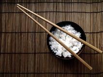 Een kom die rijst een nietje in Aziatisch voedsel vertegenwoordigt Stock Afbeelding