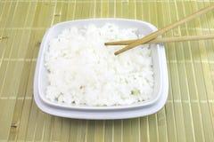 Een kom gekookte witte rijst met eetstokjes op bamboeachtergrond royalty-vrije stock afbeeldingen