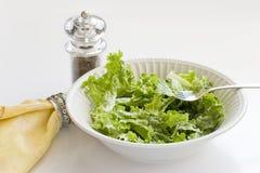 Een kom groene salade en peppermill Stock Foto's