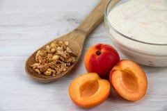 Een kom met abrikozenyoghurt wordt gevuld en een houten lepelhoogtepunt van gr. die Stock Afbeelding