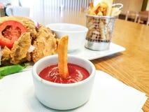 Een kom tomatenketchup met een Friet die zich daarin bevinden - Snel voedselrestaurant royalty-vrije stock foto