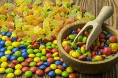 Een kom van boom met snoepjes van diverse kleuren op een houten achtergrond, Stock Foto