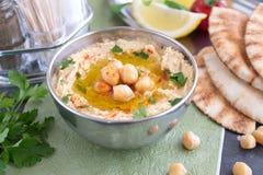 Een kom van hummus met ingrediënten: kekers, komijn, citroenknoflook en peterselie royalty-vrije stock afbeeldingen