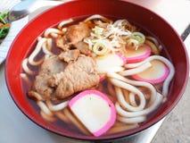 Een kom van udonnoedels met gesneden varkensvlees en KAMABOKO worden bedekt die royalty-vrije stock afbeelding