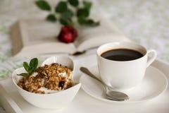 Een kom yoghurt en granola, een kop van koffie op een wit dienblad op het bed, op de achtergrond een open boek met een rood namen Stock Afbeelding
