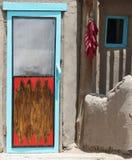 Een Koord van Peper Hung Outside een Pueblo-Deur stock foto