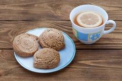 Een kop geurige thee met citroen en eigengemaakte koekjes met sesa royalty-vrije stock afbeeldingen