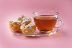 Een kop groene thee en drie die profiteroles met suikerpoeder wordt bestrooid op een roze achtergrond stock afbeeldingen