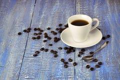 Een kop hete koffie en koffiebonen /close-up/ Stock Afbeelding