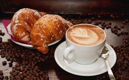Een kop hete koffie en twee verse croissants op de lijst, op de oppervlakte waarvan koffiebonen, een vers ontbijt verspreidde Royalty-vrije Stock Afbeelding