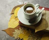Een kop koffie en bladeren stock fotografie