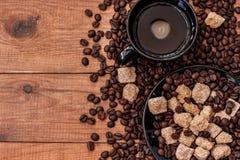 Een Kop koffie, rietsuiker en koffiebonen op houten lijst Stock Afbeelding