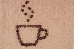 Een kop koffiebonen met rook. Stock Foto