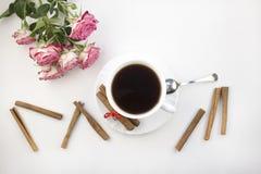 Een kop koffiekaneel en rozen op een witte ochtend als achtergrond royalty-vrije stock afbeelding
