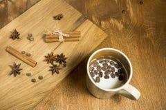 Een Kop melk en koffiebonen op de dienende houten Raad speelt anijsplant, kaneel en pimentbes mee Royalty-vrije Stock Fotografie