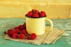 Een kop met aardbeien en frambozen op de servetten van jute op de blauw-witte houten lijst aangaande de achtergrond van Th Stock Fotografie