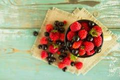 Een kop met aardbeien, frambozen en blackcurrants op de servetten van jute op de blauw-witte houten achtergrond Stock Foto's