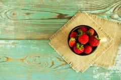 Een kop met aardbeien op de servetten van jute op de blauw-witte houten achtergrond Royalty-vrije Stock Afbeelding