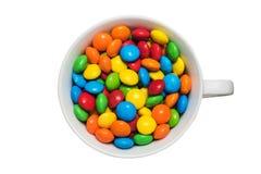 Een kop met kleurrijke smakelijke dragee op geïsoleerde bovenkant Stock Afbeeldingen