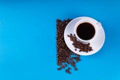Een kop met koffie naast het wordt gevuld wordt gevuld met koffiebonen, wordt de helft van de achtergrond die verlaten leeg stock afbeeldingen