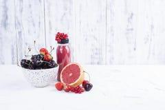 Een kop met rijpe kersen, grapefruit, frambozen, een fles sap en een witte achtergrond De zomerbessen De ruimte van het exemplaar stock foto