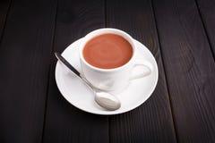 Een kop met thee en melk en een theelepeltje op een lijst binnen royalty-vrije stock foto's