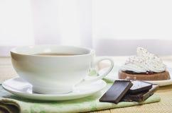 Een kop thee, een chocoladecake met eiwitroom en stukken van chocolade royalty-vrije stock afbeelding