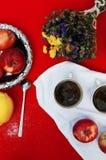 Een kop thee, citroen op een rode achtergrond, voedsel en drank, mes en vork, theetijd, de mening van de ontbijttijd van hierbove Royalty-vrije Stock Afbeelding