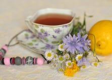 Een kop thee, de zomer een geel en blauw gebied bloeien, een citroen en een halsband op een elegante kantoppervlakte Royalty-vrije Stock Foto's