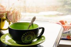 Een Kop thee of een koffie voor het venster royalty-vrije stock afbeelding