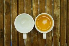 Een kop thee & een lege ceramische kop op houten lijst Stock Foto