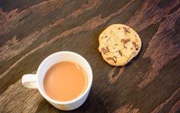 Een kop thee en een chocoladeschilferkoekje stock foto