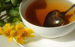 Een kop thee en gele bloemen dichtbij het Royalty-vrije Stock Afbeeldingen