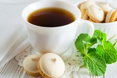 Een Kop thee en kleine koekjes met muntbladeren op een witte houten lijst royalty-vrije stock foto