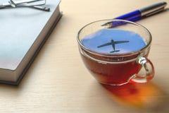 Een kop thee met een bezinning van de vliegtuigen in de hemel op het bureau stock foto's