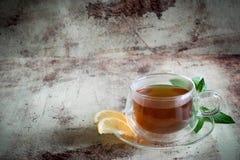 Een Kop thee met citroen en een twijg van munt op een mooie achtergrond royalty-vrije stock afbeeldingen