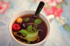 Een Kop thee met munt en kleurrijke frambozen stock fotografie