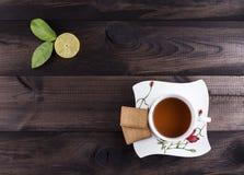 Een kop thee met theekoekjes en verse kalk op houten achtergrond Royalty-vrije Stock Foto