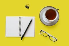 Een kop thee, een notitieboekje, een pen en oogglazen royalty-vrije stock fotografie