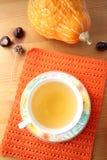 Een kop thee op sinaasappel breide mat en pompoen op houten lijst stock foto