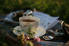 Een kop thee, parel opera-glazen in het zonsonderganglicht Stock Foto