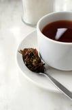 Een kop thee weet een lepelhoogtepunt van theeblaadjes. Stock Foto's