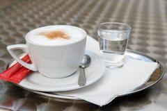 Een kop van cappuccino en een glas water Stock Afbeeldingen