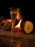 Een kop van champagne dichtbij open haard stock fotografie